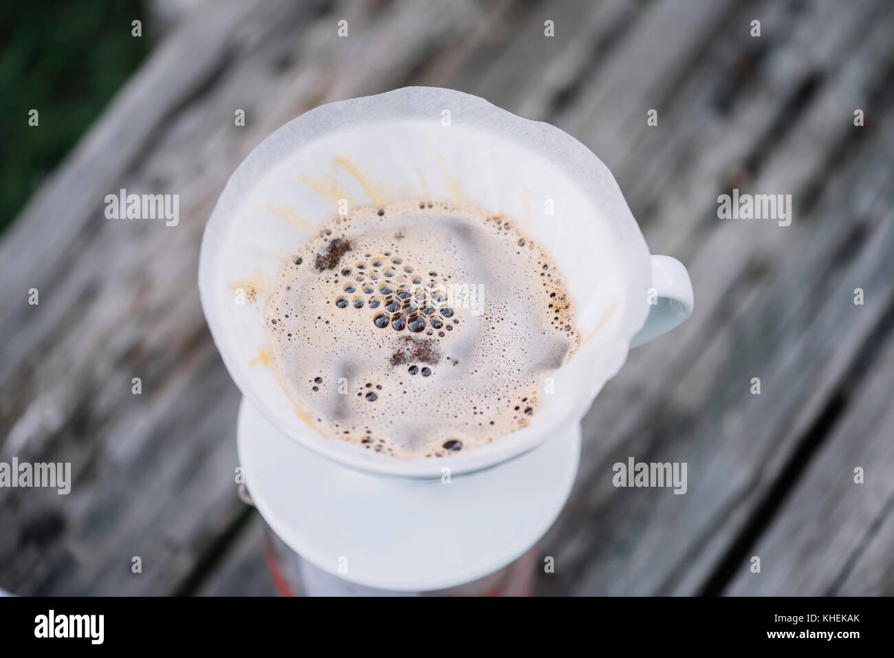 Delicious fresh morning filter coffee blooming in the dripper - Stock Image