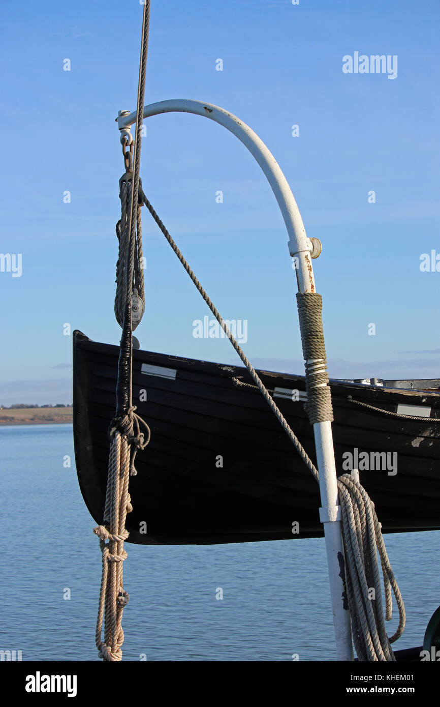 Black painted wooden lifeboat on davits. Background of river with bank in the distance and hazy blue sky. Stock Photo