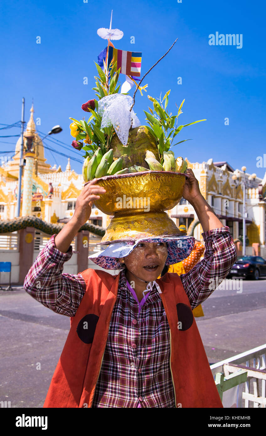 YANGON, MYANMAR -MARC 3, 2017: Woman wears on his head baskets of green bananas and coconuts for donation at Botataung - Stock Image