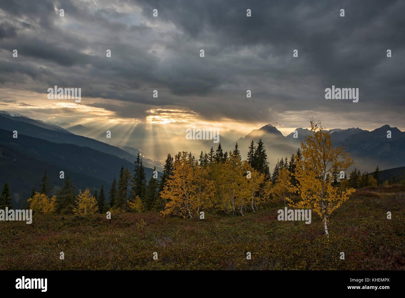 Mountain landscape in autumn, sunshine shines through cloud cover, Inn Valley, Tyrol, Austria - Stock Image
