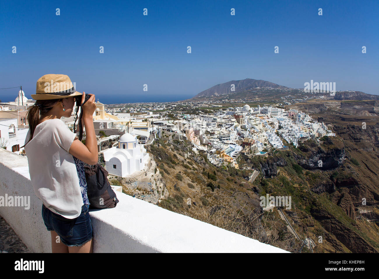 Woman photographing at a view point, crater edge path at the town Thira, Santorin island, Cyclades, Aegean, Greece Stock Photo