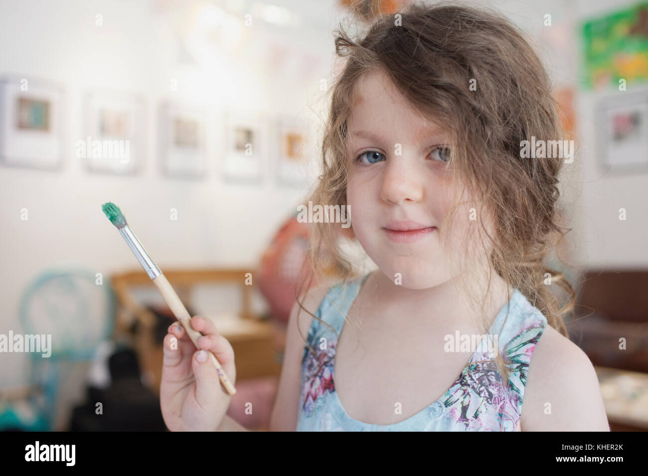A girl holding a paintbrush - Stock Image