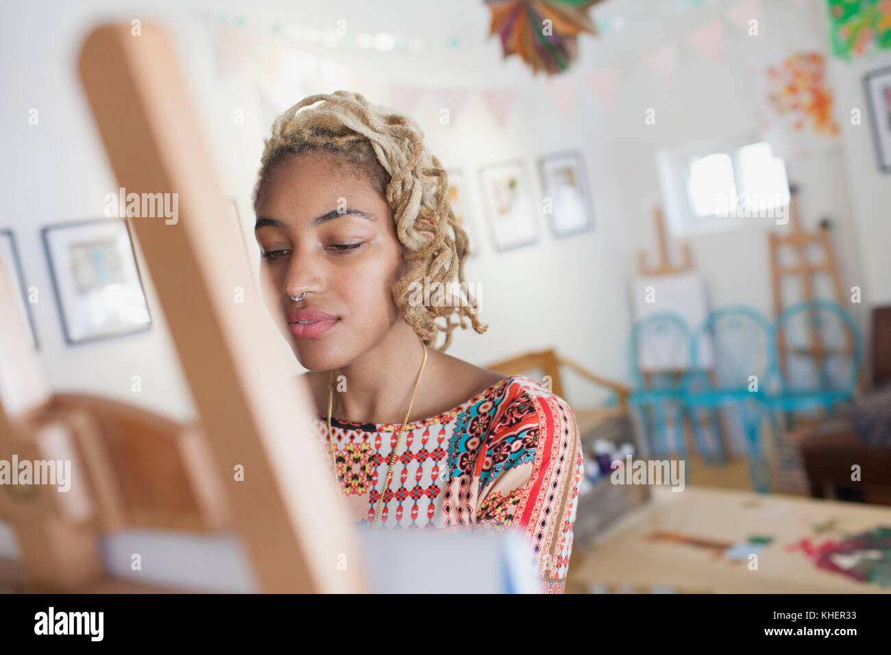 A young woman in front of an easel - Stock Image