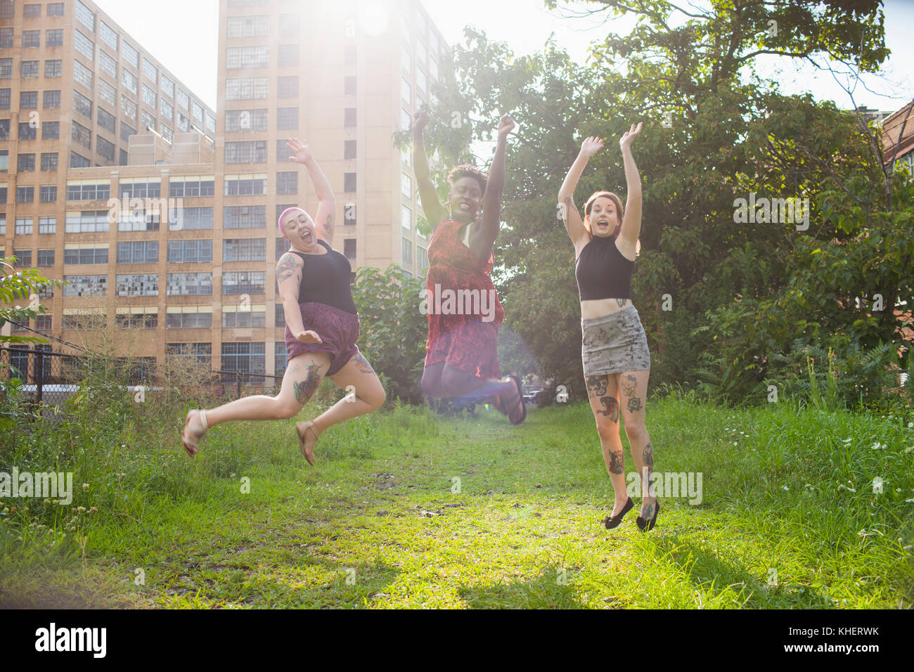 Three young women jumping - Stock Image