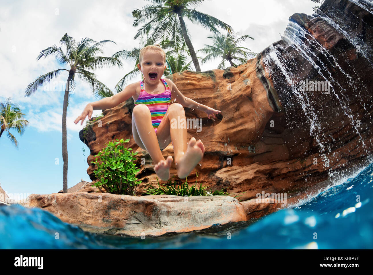 Funny child learn to swim with fun. Girl jumping high with splashes into water pool under waterfall. Healthy lifestyle, - Stock Image