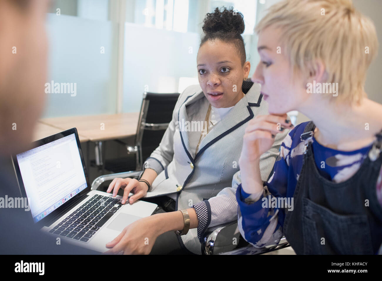 Group of young professionals collaborating in office with their laptops - Stock Image