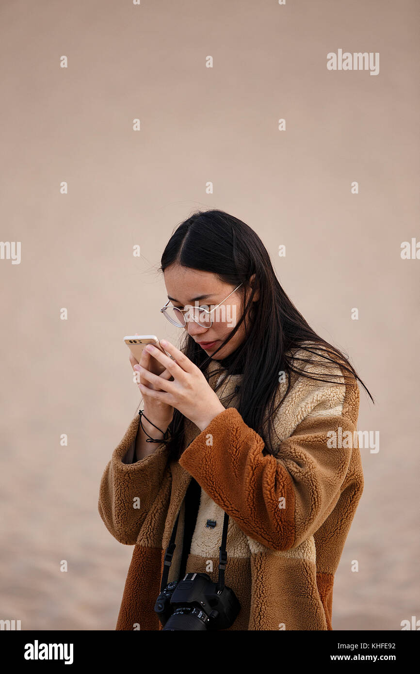 Dunhuang,China - October 13,2017: Young china looks self-absorbed to her cell on October 13, China. - Stock Image