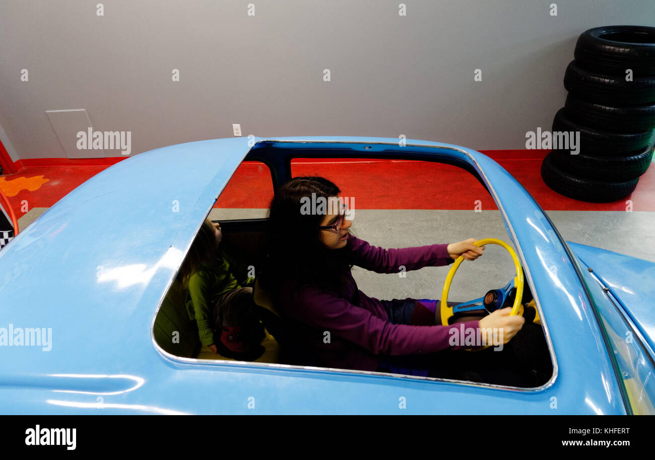 A mother pretending to drive a Fiat 500  in the Musee D'Enfance indoor themed play cenrtre in Laval, Quebec - Stock Image