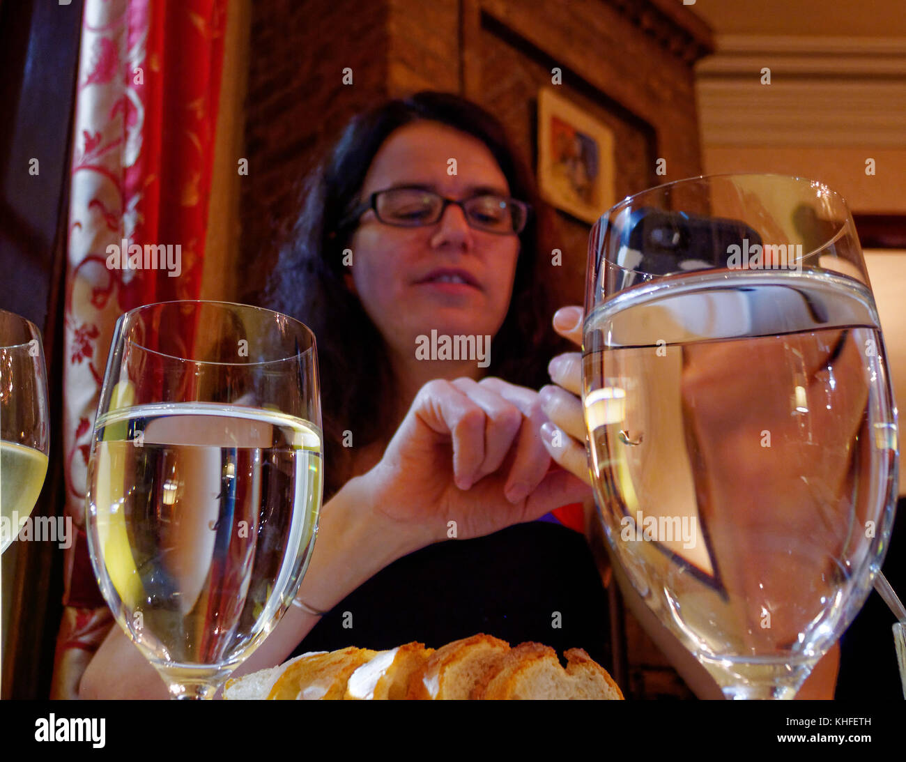 A woman using a mobile phone sat at a table ina restaurant - Stock Image