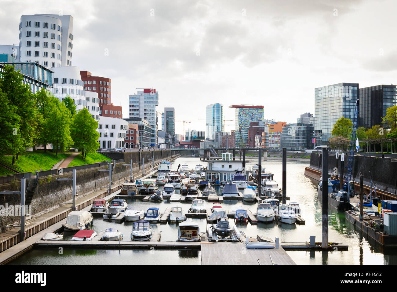 Cloudy day in Dusseldorf's harbour. Cityscape view on Medienhafen full of boats - Stock Image