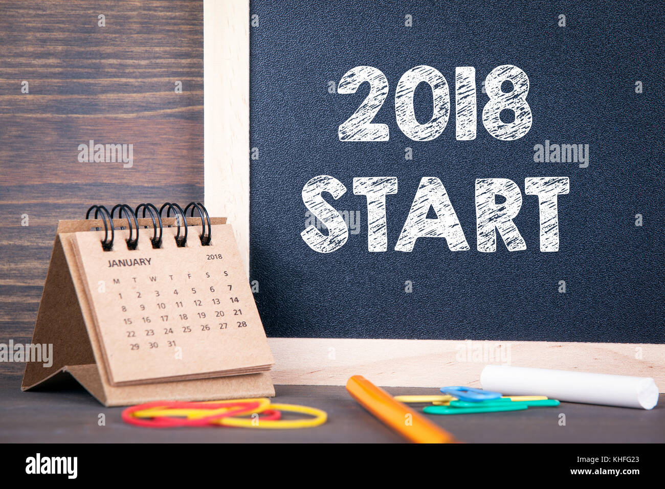2018 start. paper calendar and chalkboard on a wooden table - Stock Image