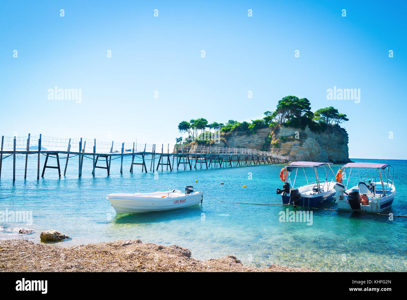 Amazing seascape with azure sea water and wooden bridge leading to the exotic island. Lifeboats picturesquely moored - Stock Image
