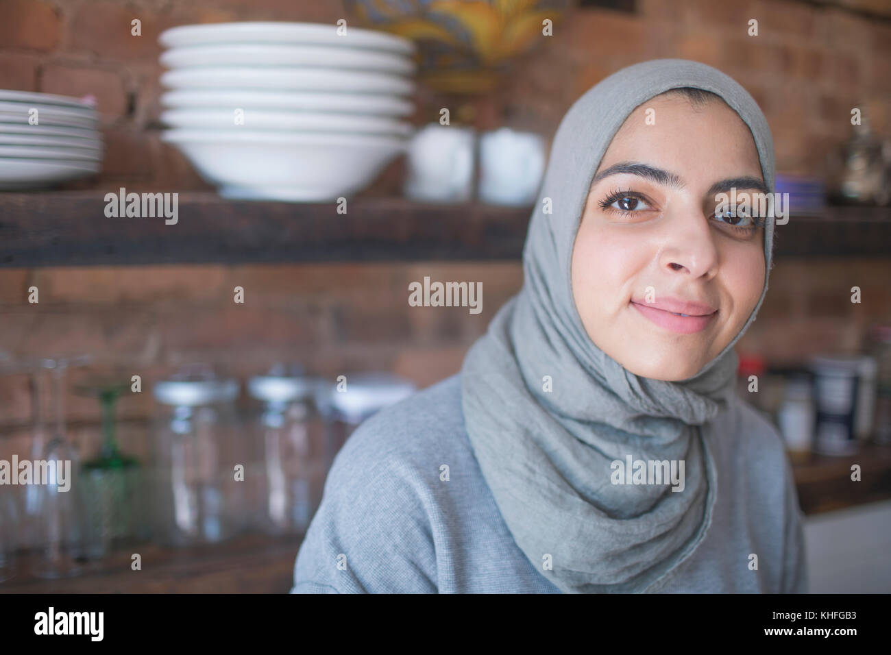 Muslim businesswoman wearing a hijab in her kitchen - Stock Image