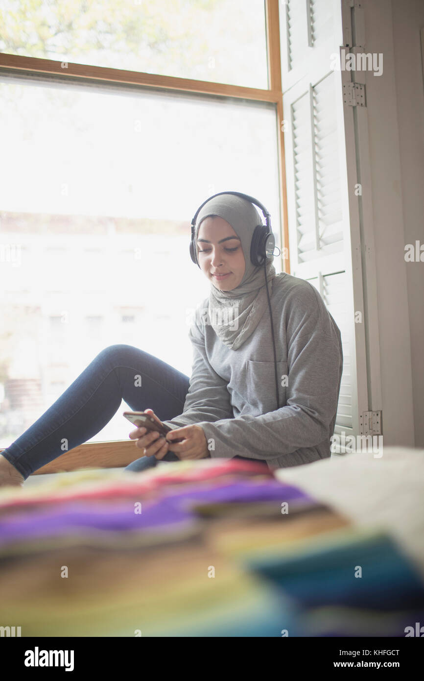 Muslim woman wearing a hijab listening to music - Stock Image