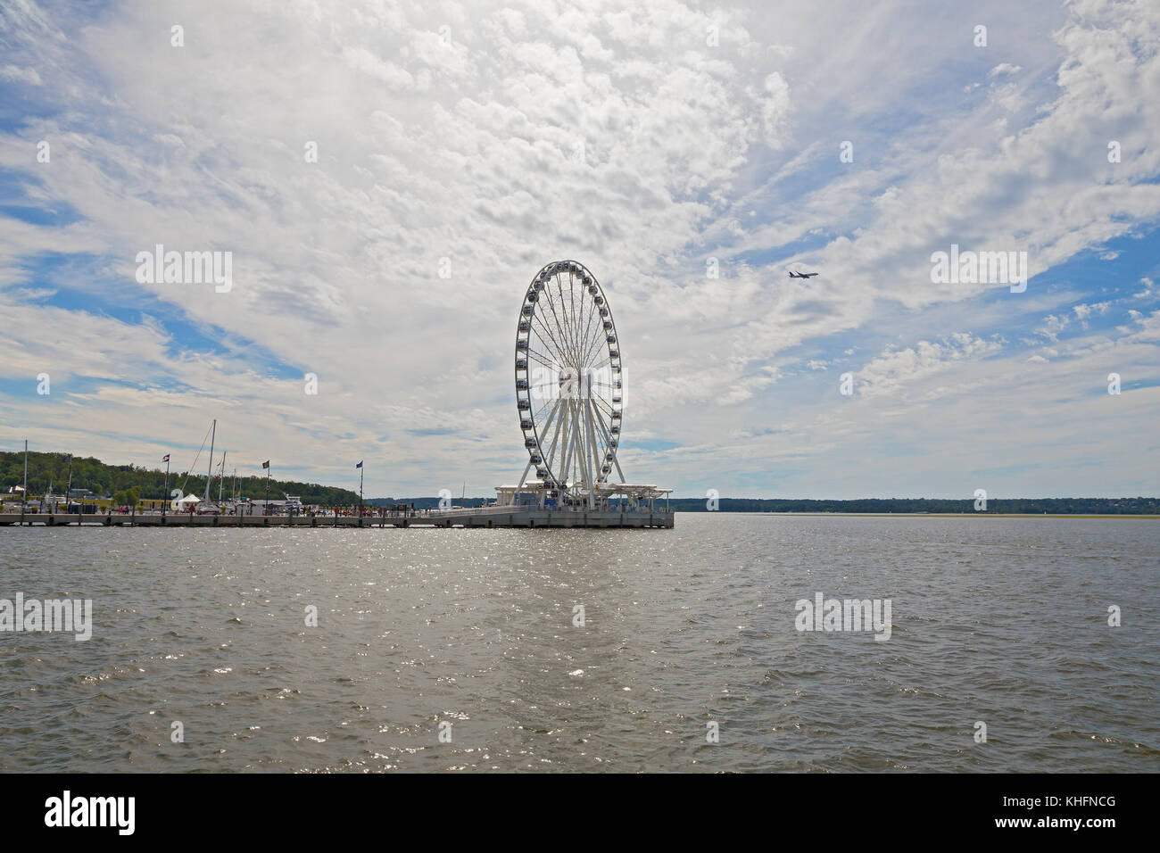 Sun shines through cumulus clouds on the Ferris of National Harbor in Oxon Hill, Maryland, USA. National Harbor - Stock Image
