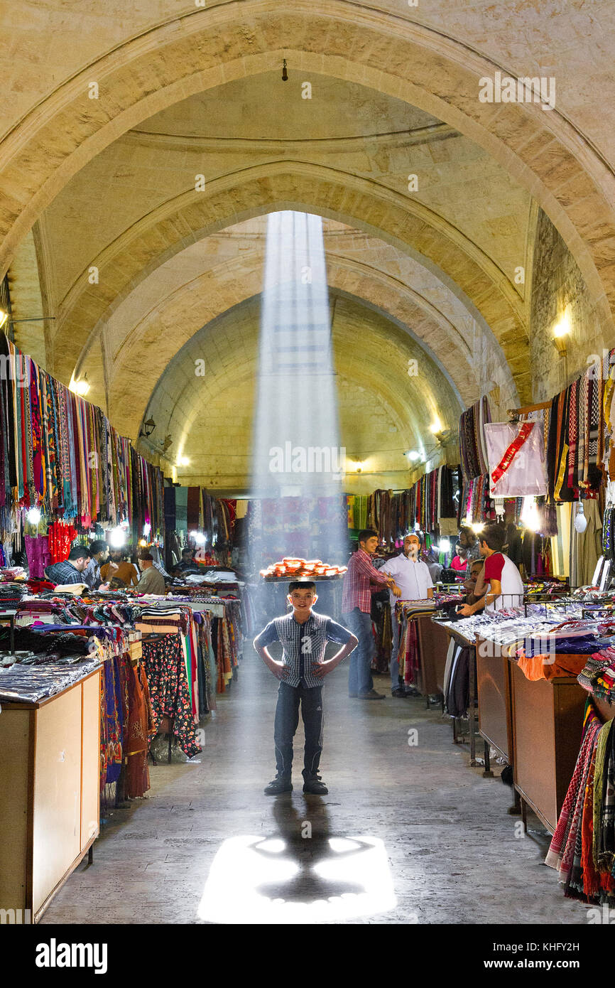Boy selling sesame bread known as Simit, under the beam of light in the Gumrukhan Bazaar in Sanliurfa, Turkey. - Stock Image