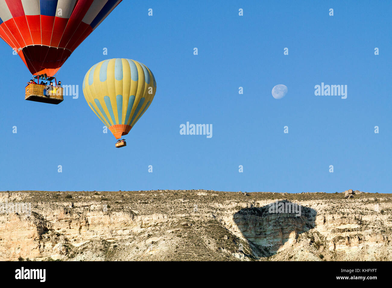 Hot air balloons in the sky with the full moon, in Cappadocia, Turkey. - Stock Image