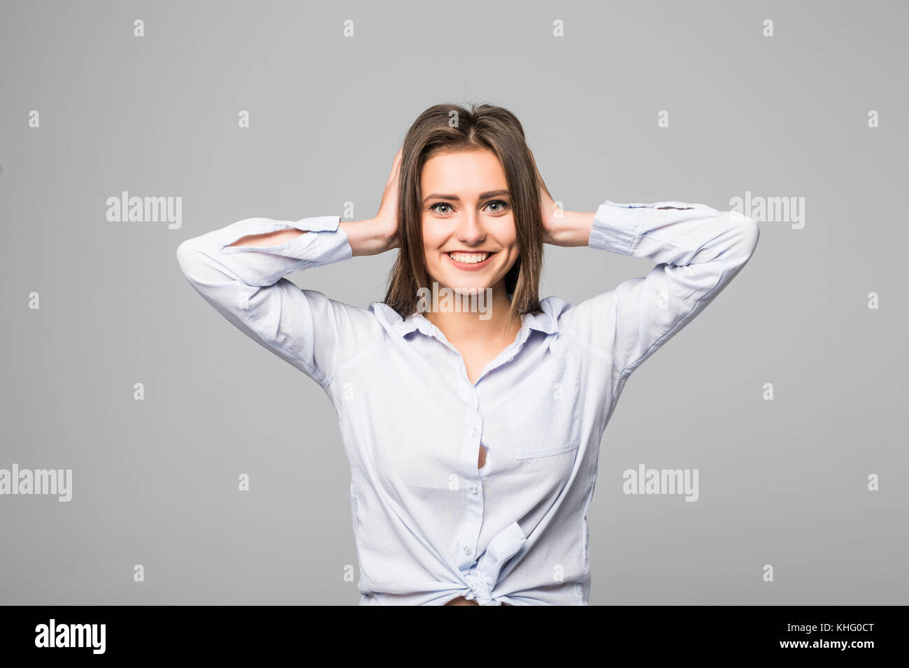 This is too much. Frustrated young woman covering ears by hands and keeping eyes closed while standing against grey - Stock Image