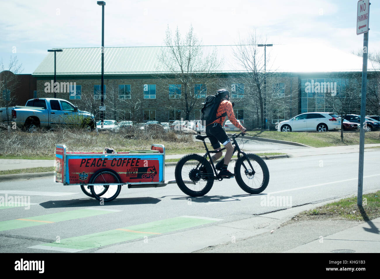 Bicycler delivering Peace Coffee to customers in a trailer pulled by the bicycle. Minneapolis Minnesota MN USA - Stock Image