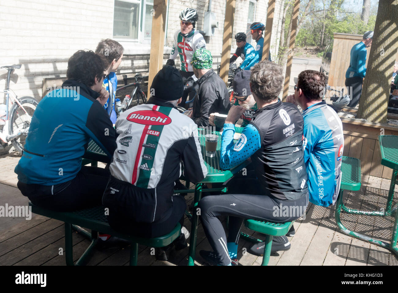 Group of men bicyclists taking a break in the Dunn Brother's Coffee Shop outdoor patio for a cup and conversation. - Stock Image