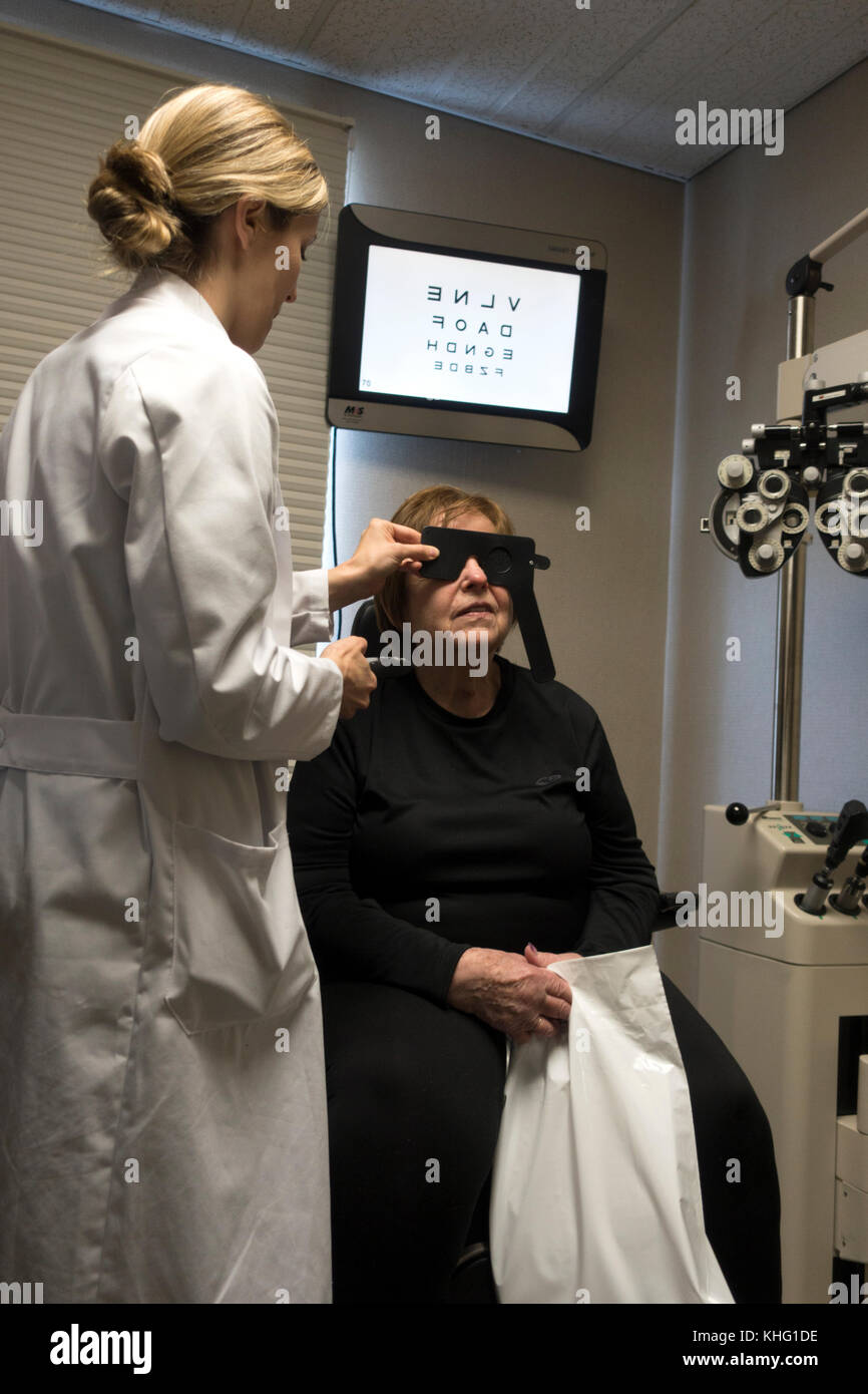 Ophthalmologist examines patient's eyes for medical treatment in the office. Minneapolis Minnesota MN USA - Stock Image