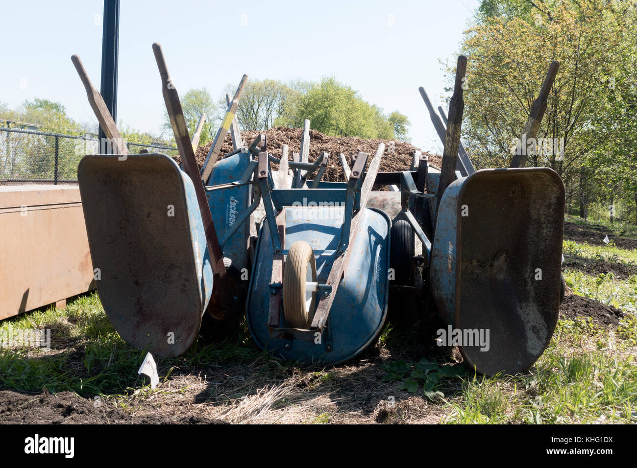 Many wheelbarrows stacked on end waiting to be used for park design near a bicycle trail. Minneapolis Minnesota - Stock Image