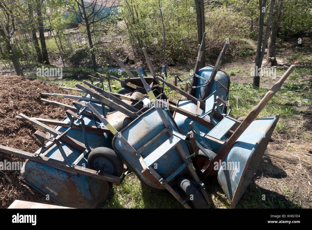 Large group of wheelbarrows used for landscaping a park alongside a bicycle trail. Minneapolis Minnesota MN USA - Stock Image