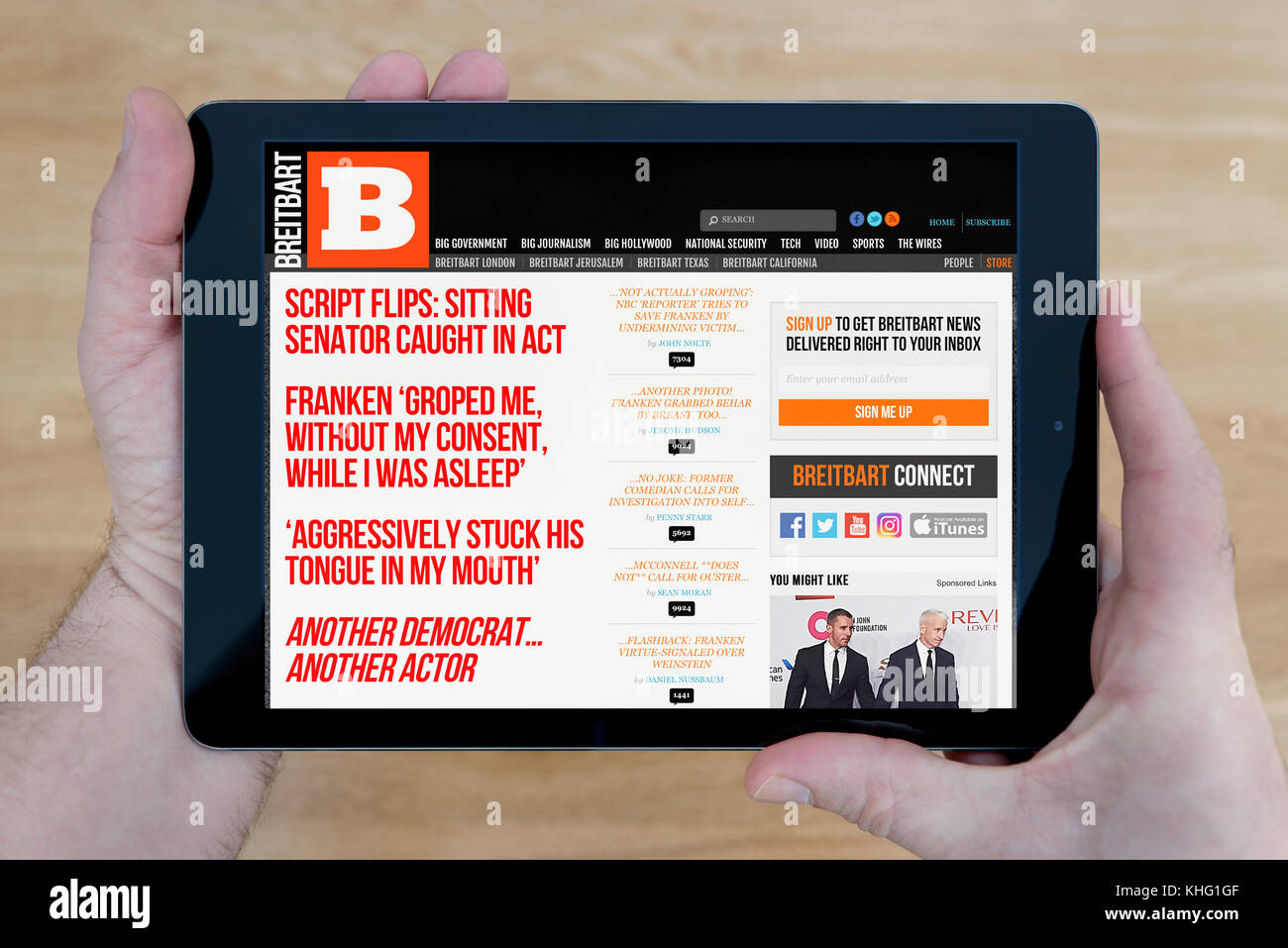 A man looks at the Breitbart website on his iPad tablet device, shot against a wooden table top background (Editorial - Stock Image