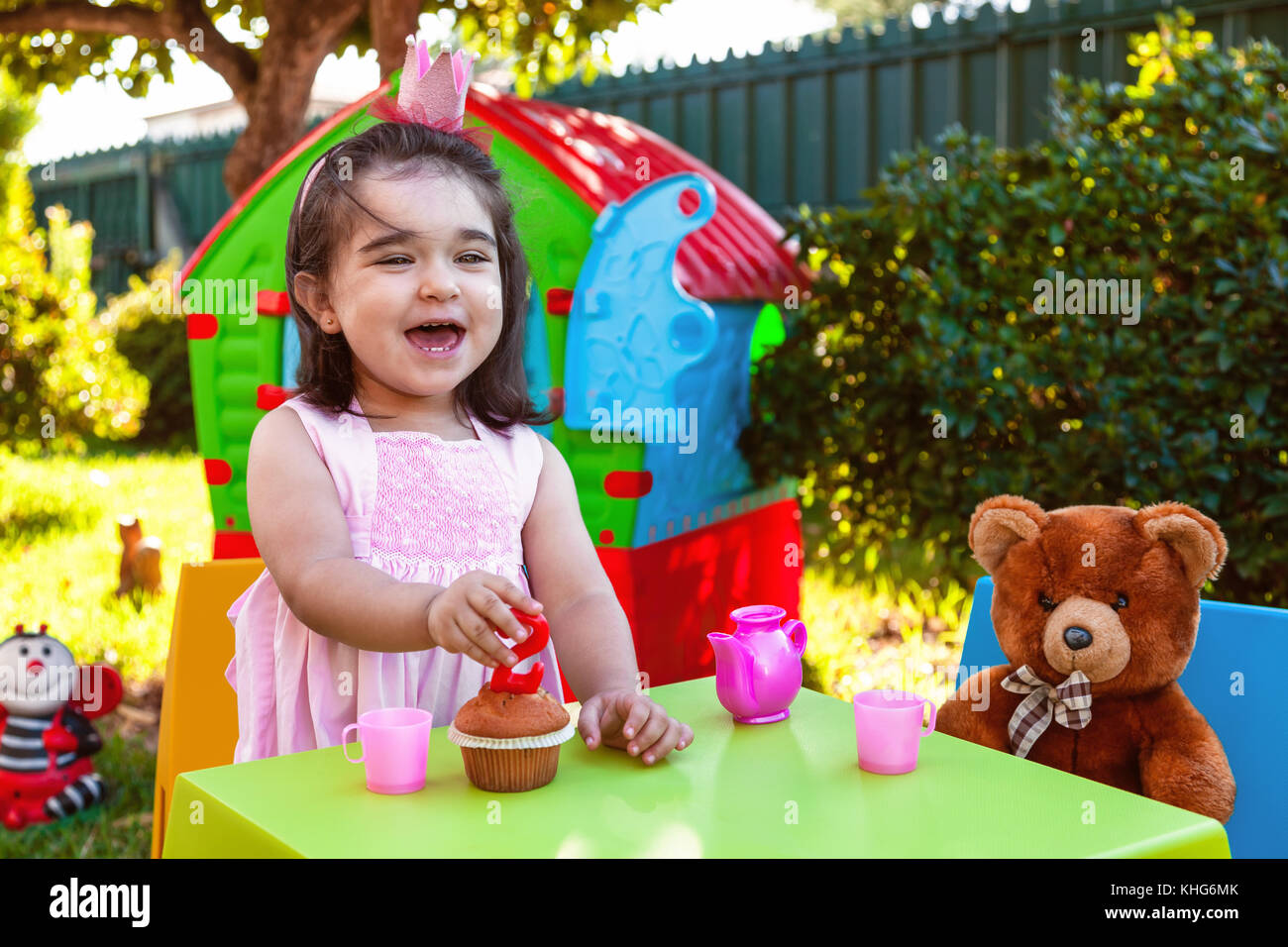Happy laughing baby toddler girl in outdoor second birthday party holding candle. Best friend Teddy Bear, playhouse - Stock Image