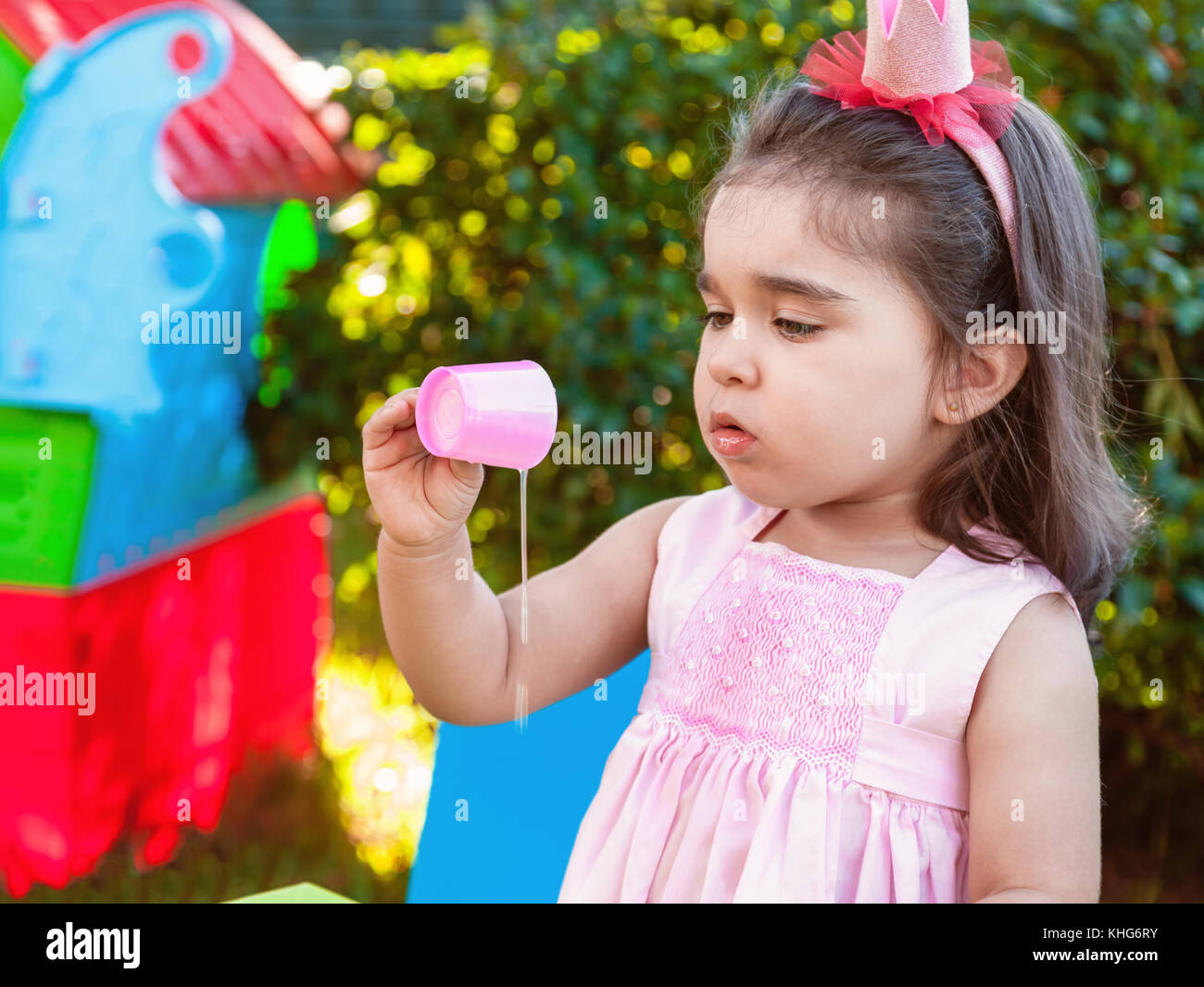 Baby toddler girl playing in outdoor experimenting and exploring by making a mess by spilling juice from cup. Pink - Stock Image