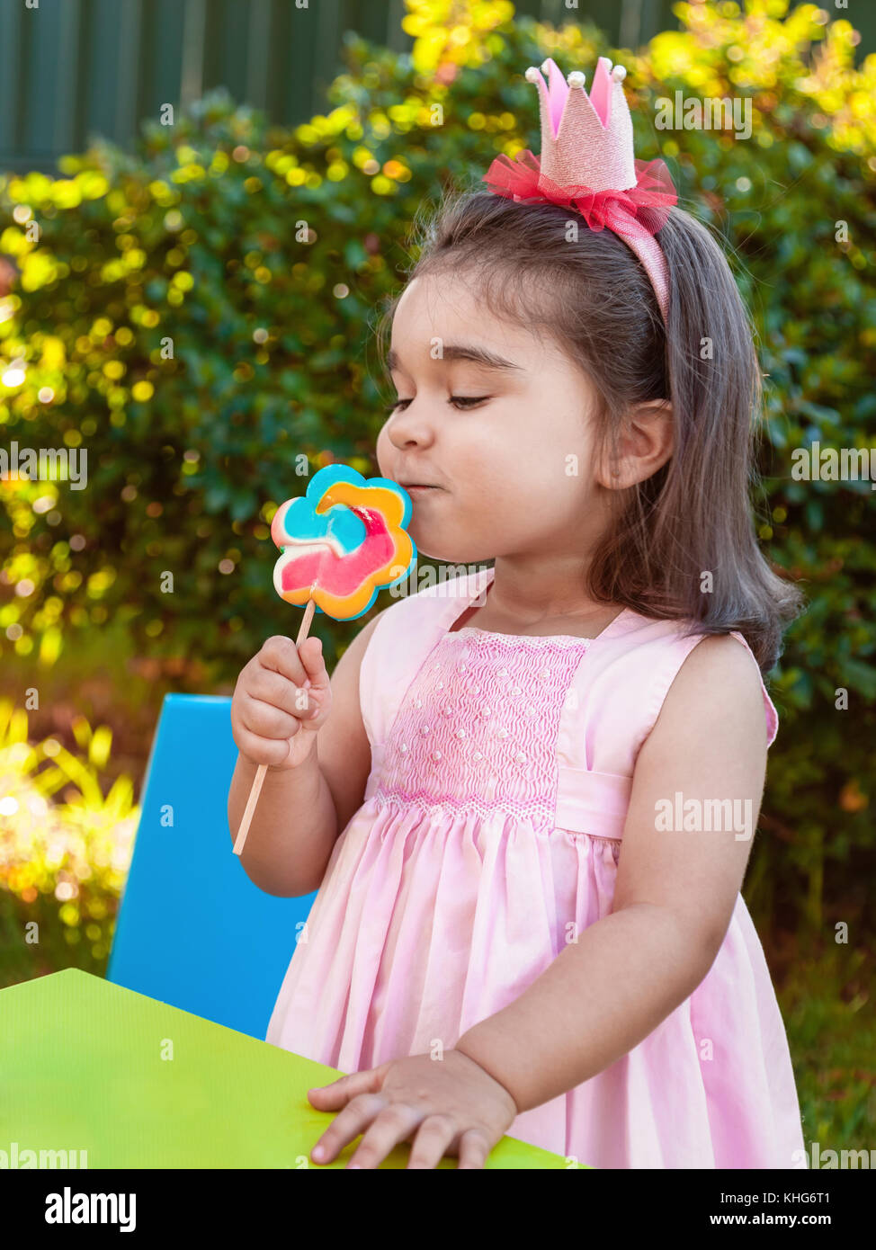 Happy baby toddler girl smelling and savoring a large colorful lollipop smell, scent or aroma dressed in pink dress - Stock Image