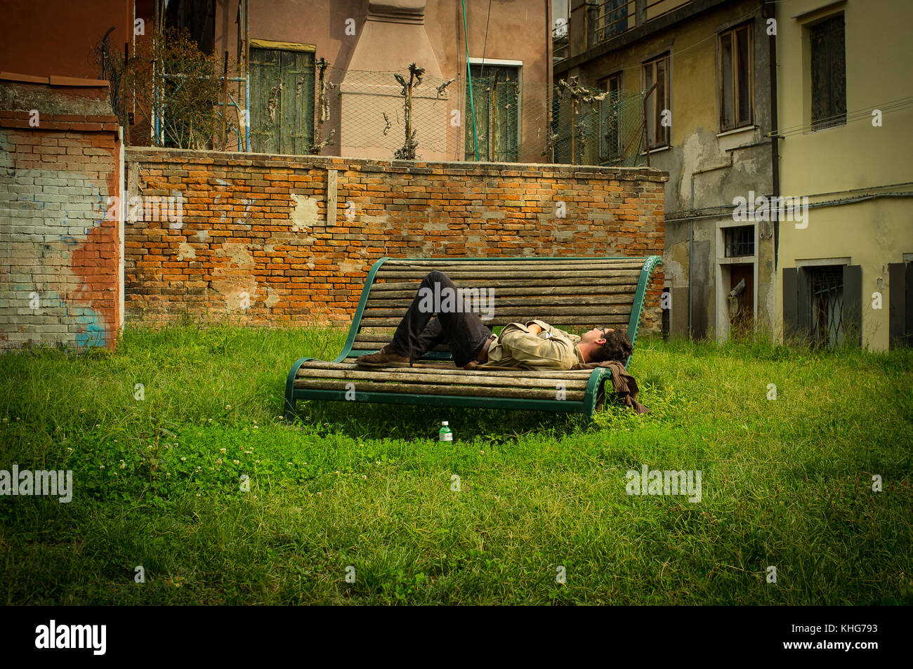 Sleeping on a bench in Venice, Have an afternoon snooz in the back streets of Venice, Green space with this city - Stock Image
