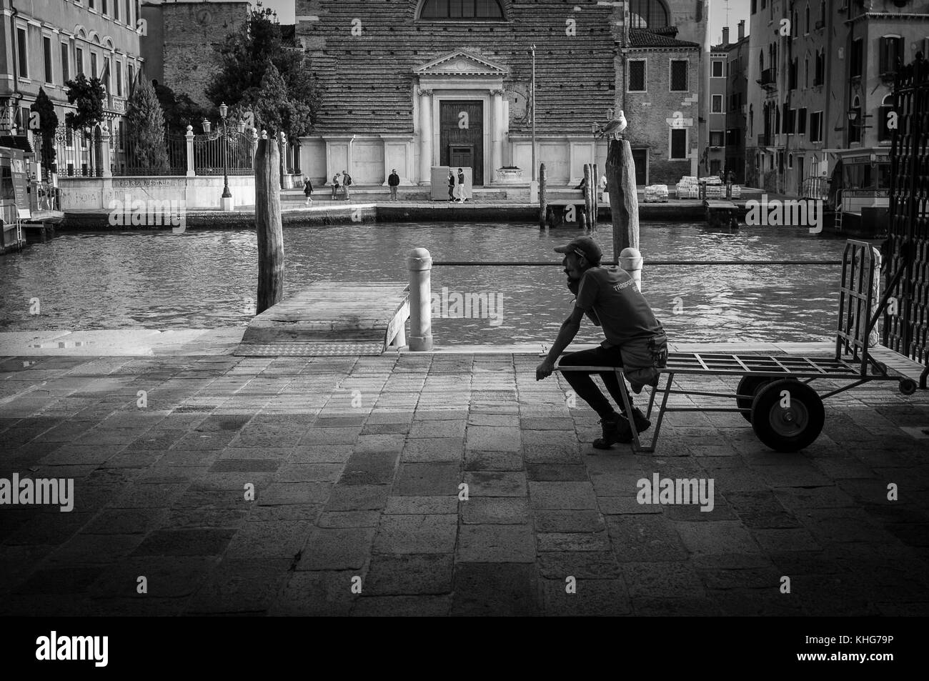 End of the working day in Venice for this delivery man or is he just waiting for the next load to be drop off for - Stock Image
