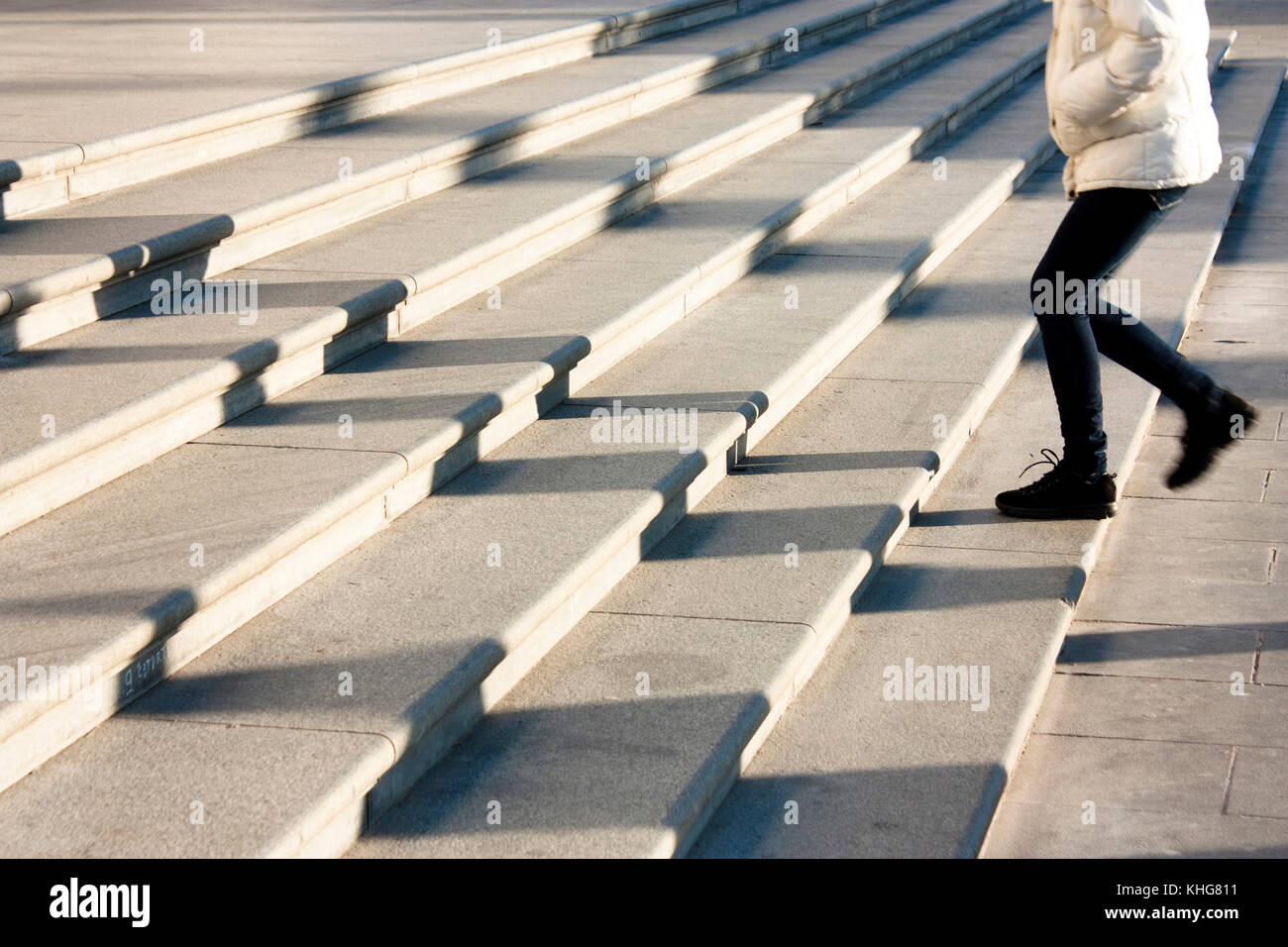One teenage girl going up the stairs in motion blur and shadows of people following , on huge public outdoor stairway Stock Photo