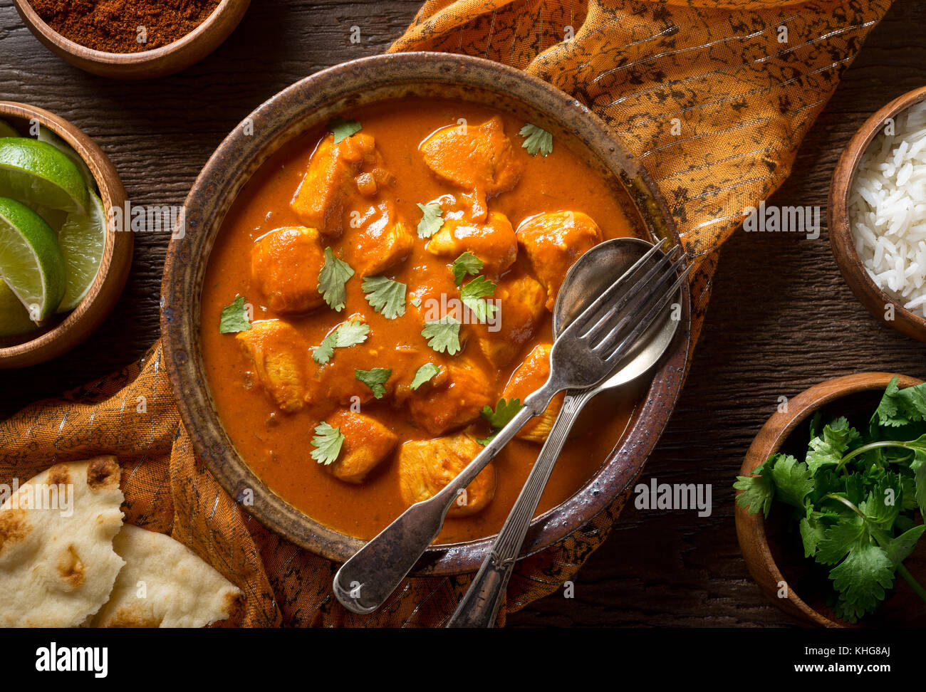 A bowl of delicious indian butter chicken curry with naan bread, basmati rice, and cilantro garnish. - Stock Image