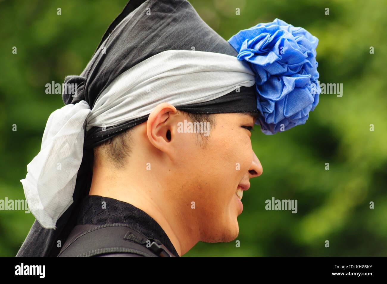 Male performer wearing a headdress on the Royal Mile during the Edinburgh International Fringe Festival - Stock Image