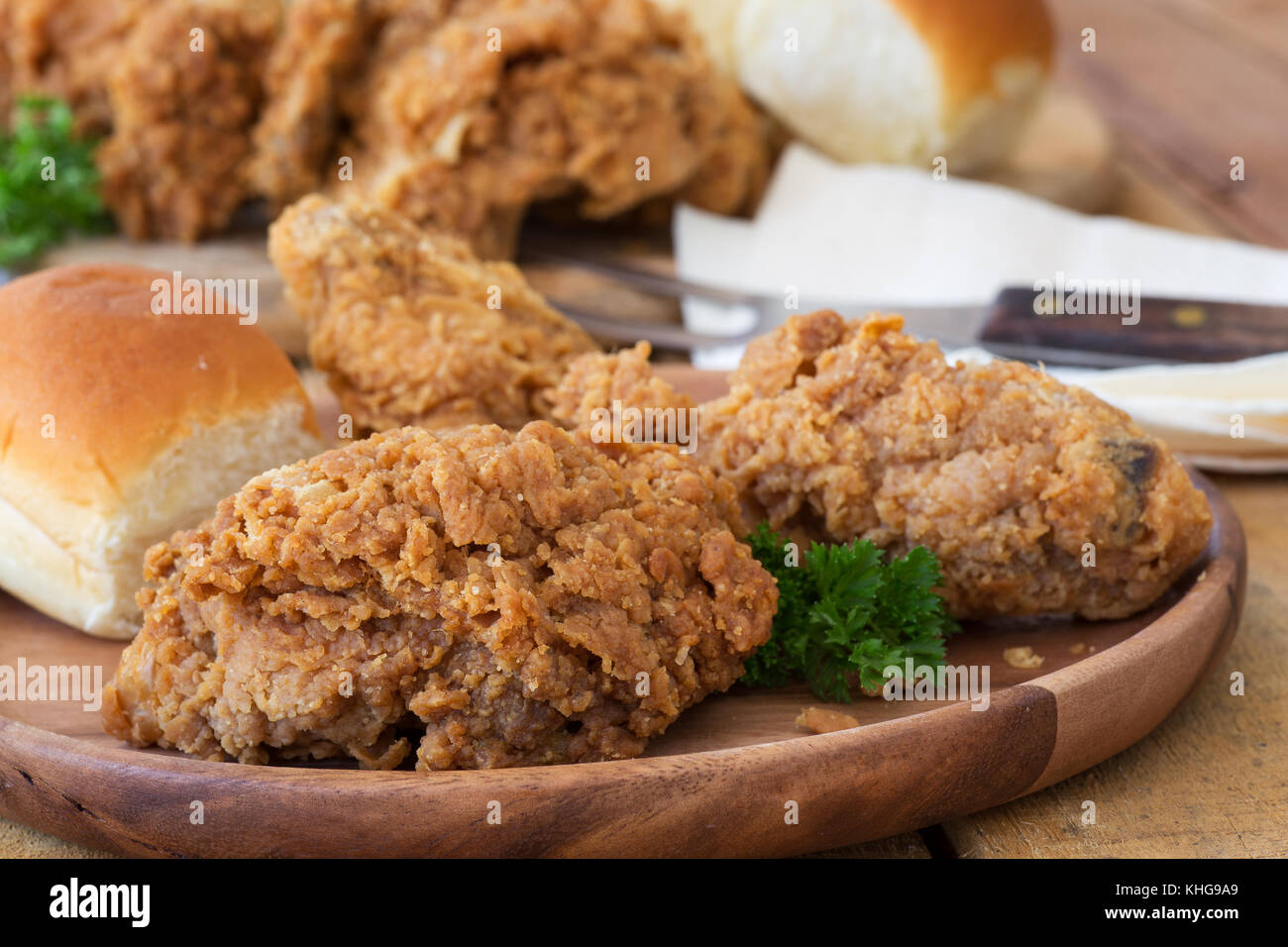 Fried chicken and dinner roll on a wooden plate - Stock Image
