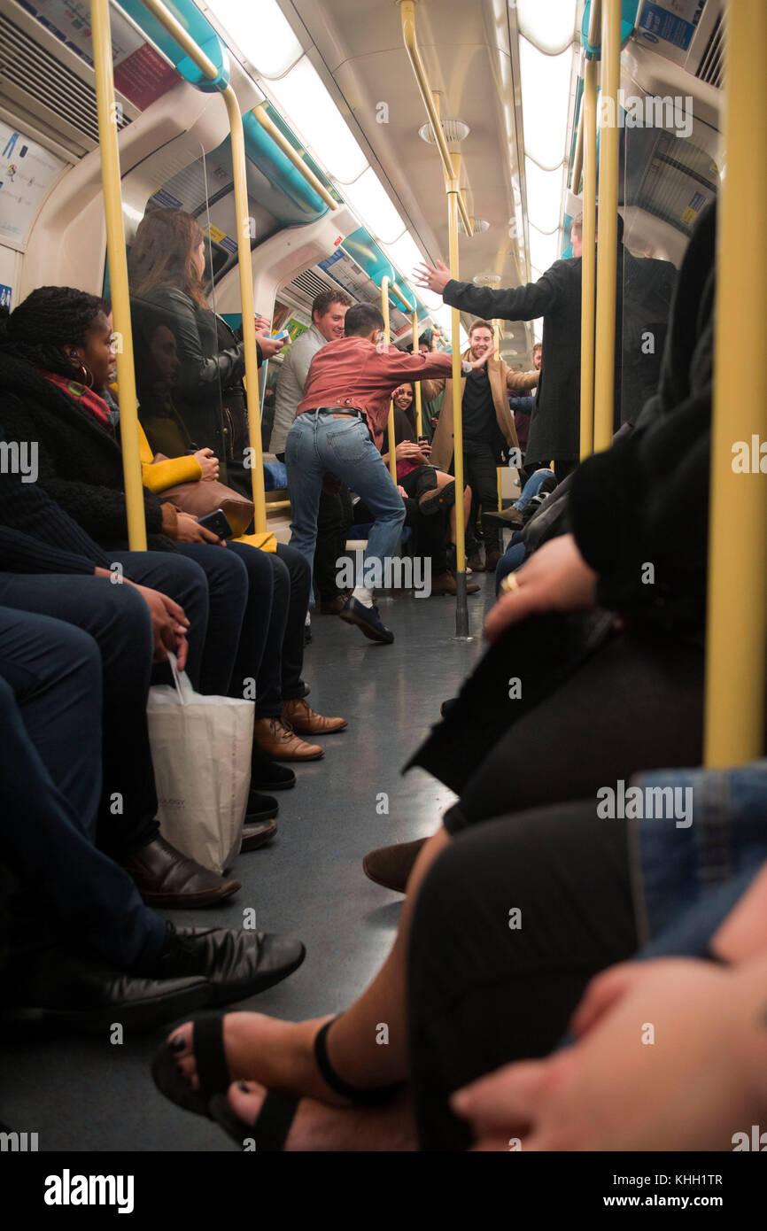 London, England, UK. 11th November 2017. Crowd of drunk people dancing on the london night tube. ©Sian Reekie - Stock Image