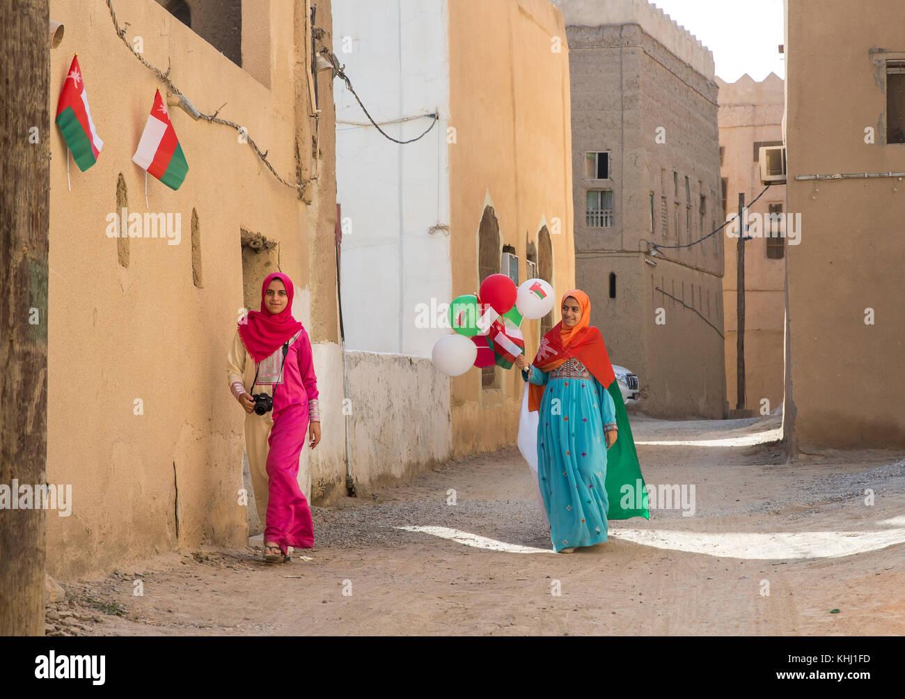 Al Hamra, Oman, November 10th, 2017: Omani girl in national dress with omani flag and baloons in celebration of - Stock Image