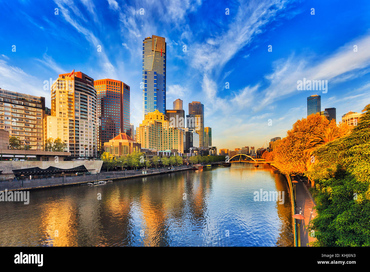 Tallest Melbourne skyscraper Eureka tower dominates South Yarra cityscape over Yarra river in warm morning sunlight - Stock Image