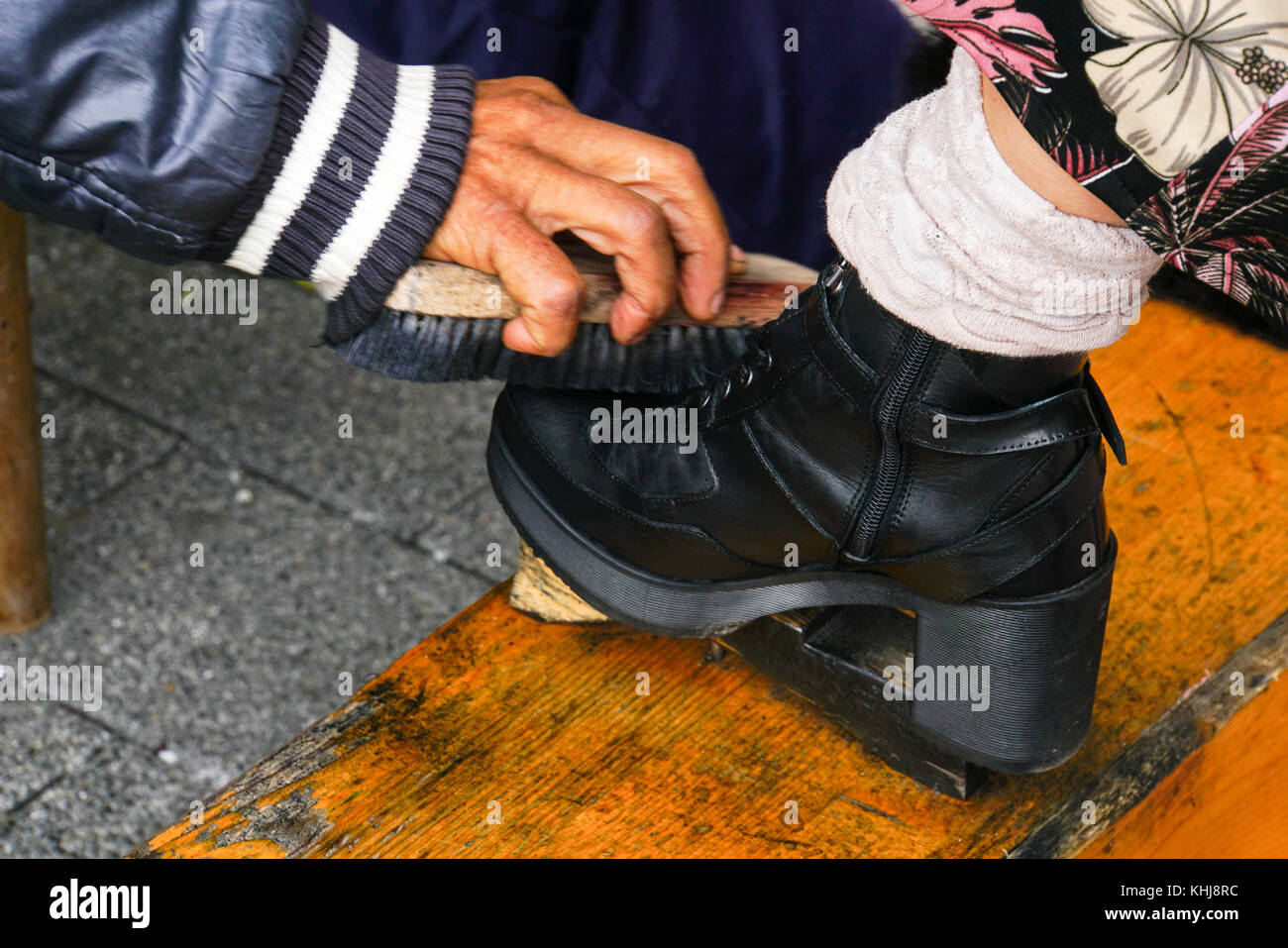 Client is having his shoe polished at a Shoeshine stand. Close-up of the hand, brush and boot, Photographed in Plovdiv, - Stock Image
