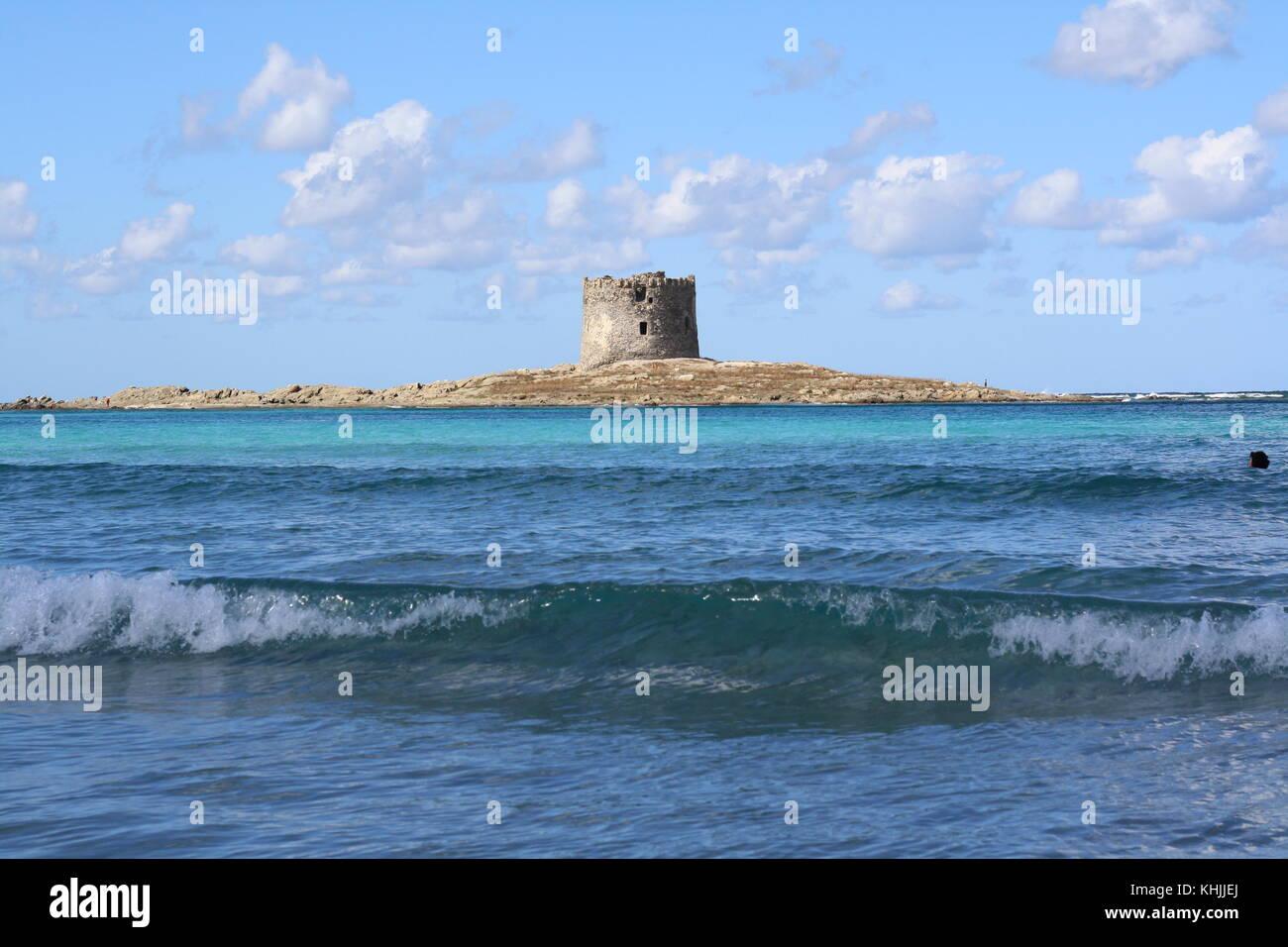 A stone tower called nuraghe on La Pelosa beach in Sardinia. - Stock Image