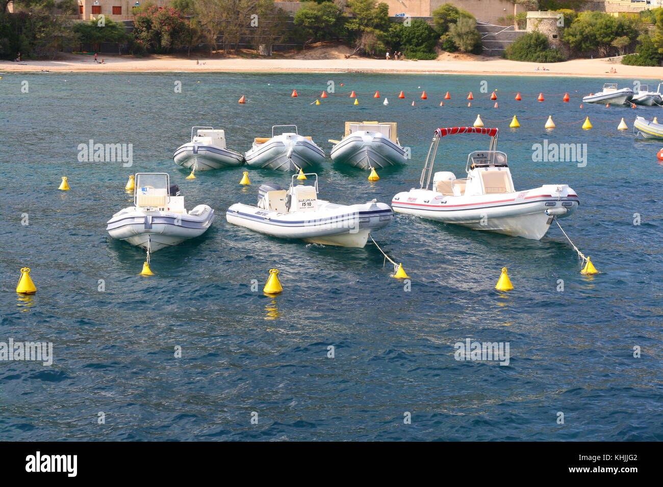 Small inflatable motorboats anchored on open sea. - Stock Image