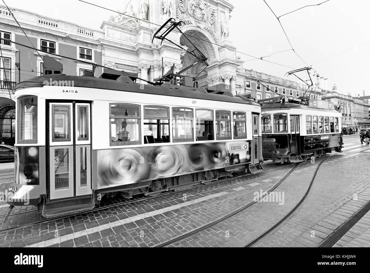 Nostalgic trams stopping at Triumph Arch, Lisbon - Stock Image