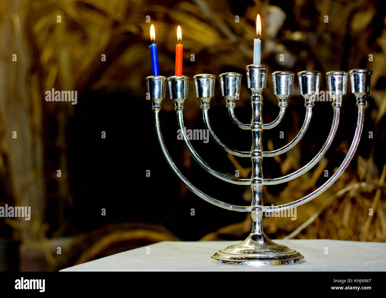 A Chanukia the main symbol of Chanukah, The Jewish festival of light with 3 lit candles for the second day - Stock Image
