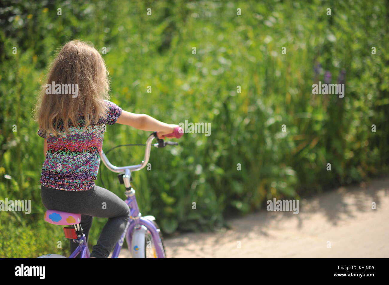 Girl rides velocipede on a country road. - Stock Image