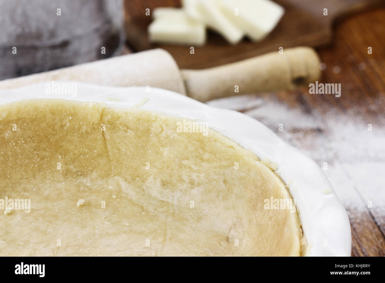 Homemade pastry s with rolling pin, sifter and butter in background. Extreme shallow depth of field with selective - Stock Image