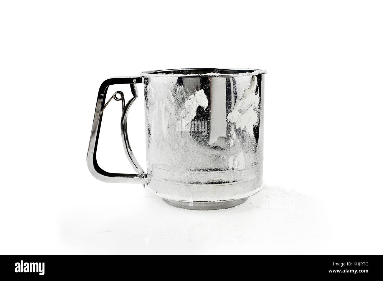 Metal flour sifter with flour dusted on the side and beneath isolated over a white background. - Stock Image