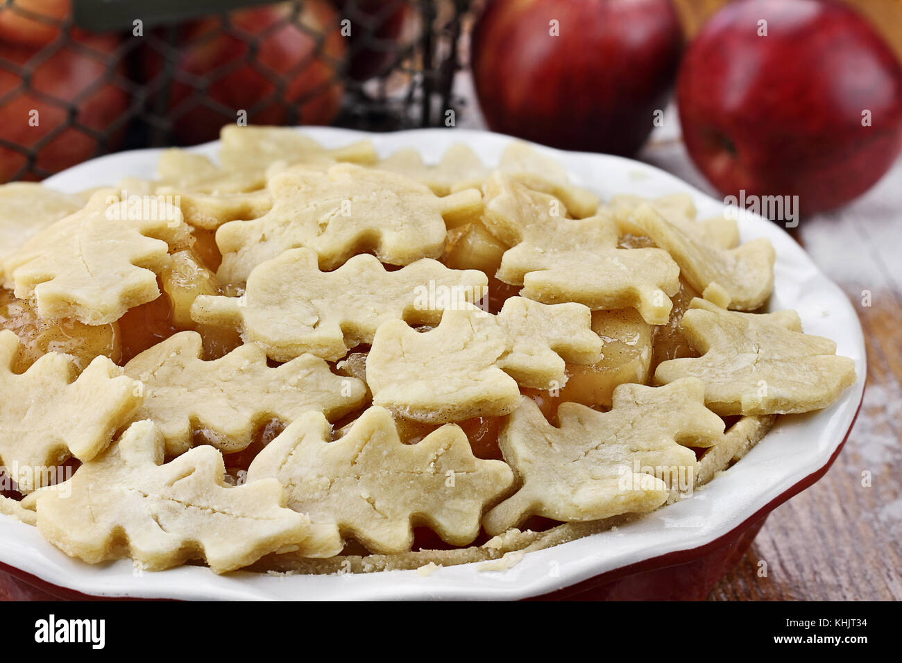 Raw, unbaked apple pie with top crust cut out in the shape of autumn leaves. Shallow death of field with selective - Stock Image