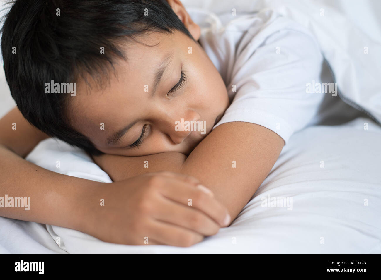 boy sleeping on bed with white sheet and pillow.asian kid fall asleep daydreaming.sleep concept - Stock Image